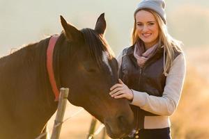 junge Frau streichelt Pferd foto