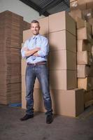lächelnder Manager mit verschränkten Armen im Lagerhaus foto