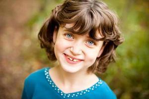 glückliches, junges Mädchen, das in die Kamera lächelt, im Freien foto