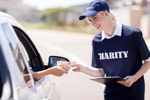 junge Wohltätigkeitsarbeiterin erhält Spende foto