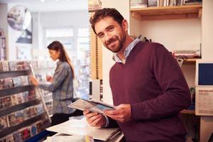 Mann, der hinter der Theke in einem Plattenladen arbeitet, Porträt foto