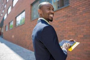 der schwarze Geschäftsmann mit Laptop foto