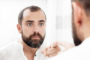Mann, der sich im Spiegel ansieht und zeigt foto