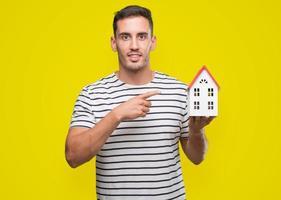 hübscher Immobilienmakler, der ein Haus sehr glücklich hält, mit Hand und Finger zeigend