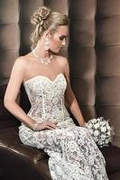 Porträt einer glücklichen schönen Braut, die auf Stuhl sitzt foto