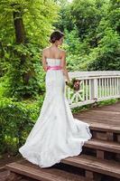Braut im Park auf der Brücke