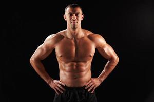 lächelnder männlicher Bodybuilder mit nacktem Oberkörper und Händen auf den Hüften foto