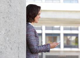 Geschäftsfrau, die Textnachricht auf Handy liest foto