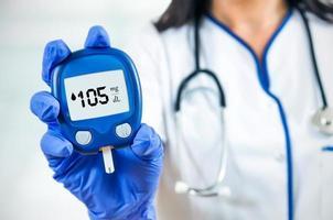 Nahaufnahmezusammensetzung der Ärztin, die Glukometer hält. foto