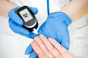 Ärztin, die Blutzuckerspiegelblut in der Krankenhausnahaufnahme misst foto