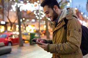 Porträt des jungen Mannes, der sein Handy nachts benutzt. foto