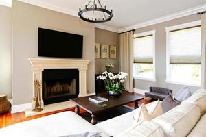 helles luxuriöses Wohnzimmer mit Kamin und Fernseher foto
