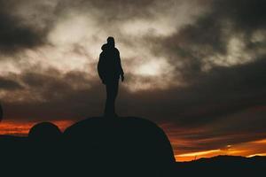 Mann, der während der goldenen Stunde auf Felsen steht foto