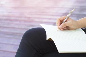 Nahaufnahme der Person, die in Notizbuch schreibt