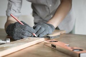 Nahaufnahme des Zimmermanns, der Holz misst