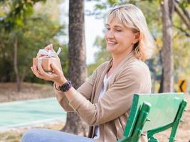 Frau, die Geschenk in einem Park öffnet