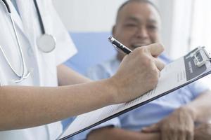 Arzt macht sich Notizen in der Zwischenablage für den Patienten