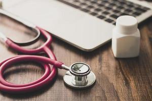 Stethoskop und Tablettenfläschchen neben Laptop foto