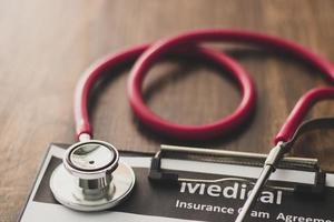 rotes Stethoskop und Zwischenablage auf dem Tisch foto