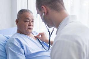 Arzt, der mit einem Stethoskop auf das Herz des Patienten hört foto