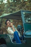 junger Mann sitzt in einem Jeep
