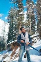 junger Mann, der im Schnee mit Regenschirm in den Händen aufwirft foto