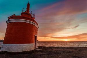 bunter Himmel und ein roter Leuchtturm foto