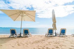 Outdoor mit Sonnenschirm und Stuhl am wunderschönen tropischen Strand und Meer