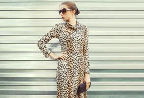 Mode hübsche Frau in Sonnenbrille und Leopardenkleid mit Handba foto