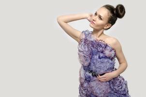 schöne Frau, die ein lila Kleid mit Spitzenblumen trägt. foto