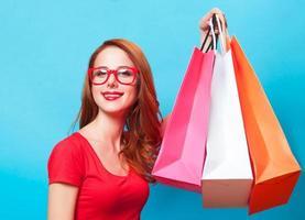rothaariges Mädchen mit Einkaufstüten auf blauem Hintergrund. foto