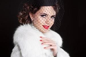 Modeporträt der eleganten Retro-Frau, die kleinen Hut trägt foto