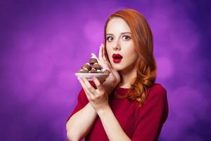 rothaarige Frauen mit Süßigkeiten auf violettem Hintergrund.