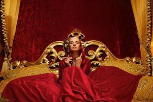 schöne Frau mit einer Karnevalsmaske, die im Bett sitzt