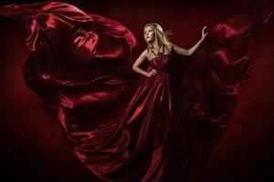 Frau im roten Kleid tanzt mit fliegendem Stoff