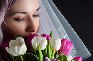 schönes Frauengesicht mit einem Strauß Tulpen foto
