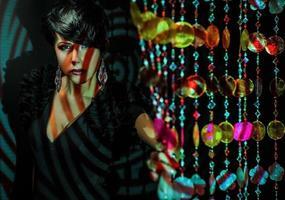 schöne brünette frau posieren auf buntem projektorlicht im studio. foto