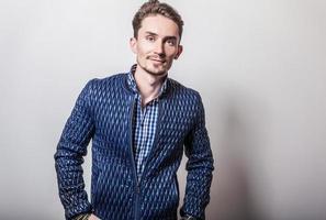eleganter junger hübscher Mann in der stilvollen dunkelblauen Jacke. foto