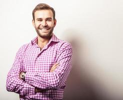 eleganter junger hübscher Mann im hellen bunten Hemd. foto