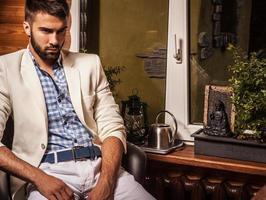 junge attraktive bärtige Männer posieren im modernen Raum. Nahaufnahmefoto. foto