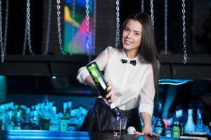 lächelnder brünetter Barkeeper, der Martini gießt foto