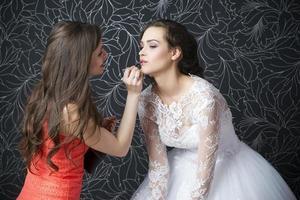 Maskenbildner wendet Lippenstift Braut an