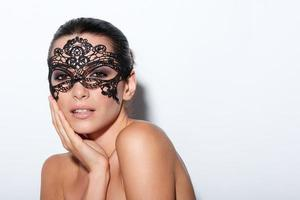 Frau mit abendlichem rauchigem Make-up und schwarzer Spitzenmaske