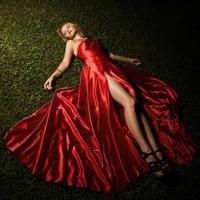 schöne Dame im roten Kleid, das auf grünem Gras liegt