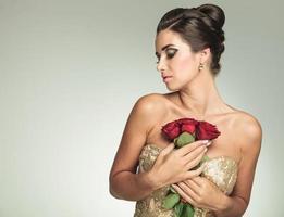 Frau hält Rosen an die Brust und schaut zur Seite foto