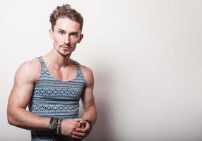 junger hübscher Mann im türkisfarbenen T-Shirt. foto