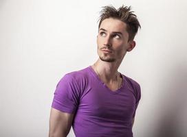 junger hübscher Mann im violetten T-Shirt.