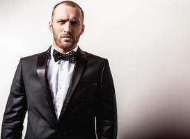 eleganter junger hübscher Mann im schwarzen Kostüm. foto