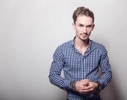 eleganter junger hübscher Mann im blau-weißen Hemd.