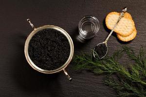 schwarzer Kaviar serviert auf Crackern mit Wodka und Zusatzstoffen foto